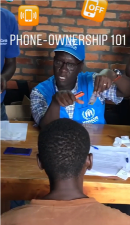 """A man in a UNHCR uniform instructs another man. Text reads """"phone ownership 101""""."""