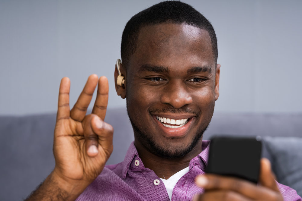 A deaf Black man using sign language on a video call