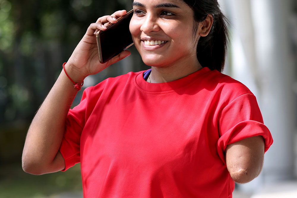 A young Indian woman with an amputated left arm using a smartphone