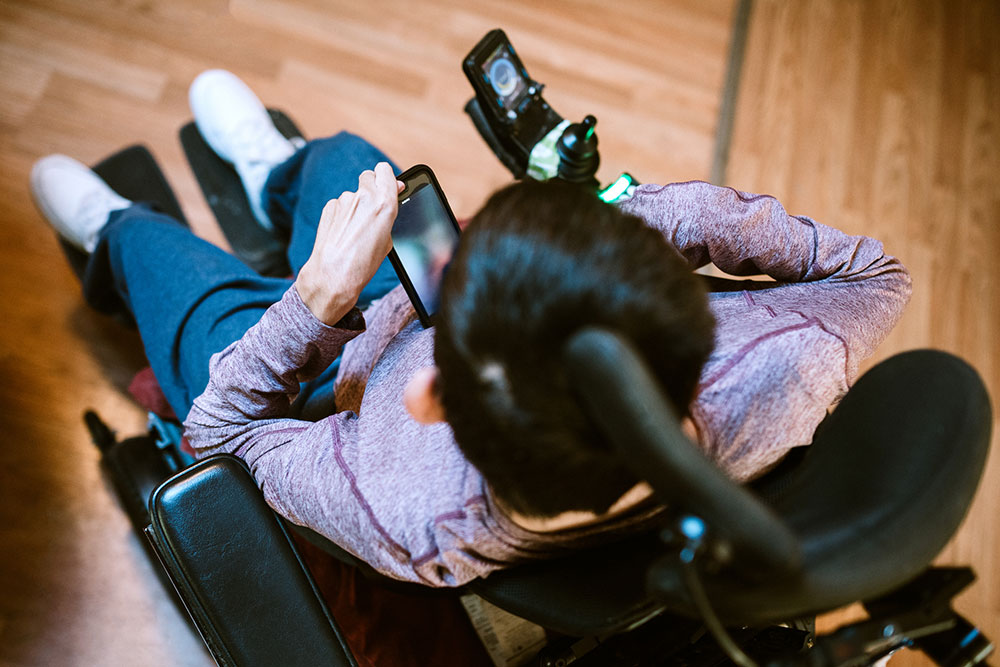 A young adult male with cerebral palsy texts someone on his smartphone, using voice recognition