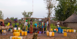 Women and children gathering to fetch water in the Koar Village, East Senegal. A solar powered telecom tower in the background provides mobile connectivity to the village.